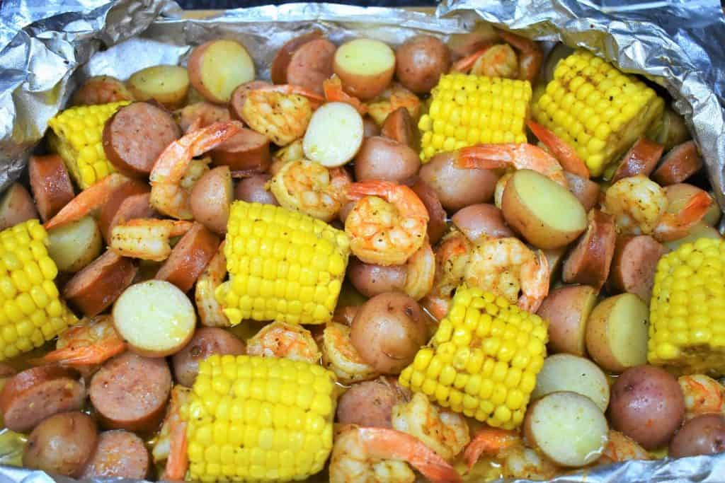 Sausage, shrimp, corn and potatoes in an open aluminum foil pack.
