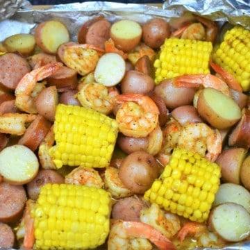 Sausage, shrimp, corn and potatoes in an open aluminum foil pack.