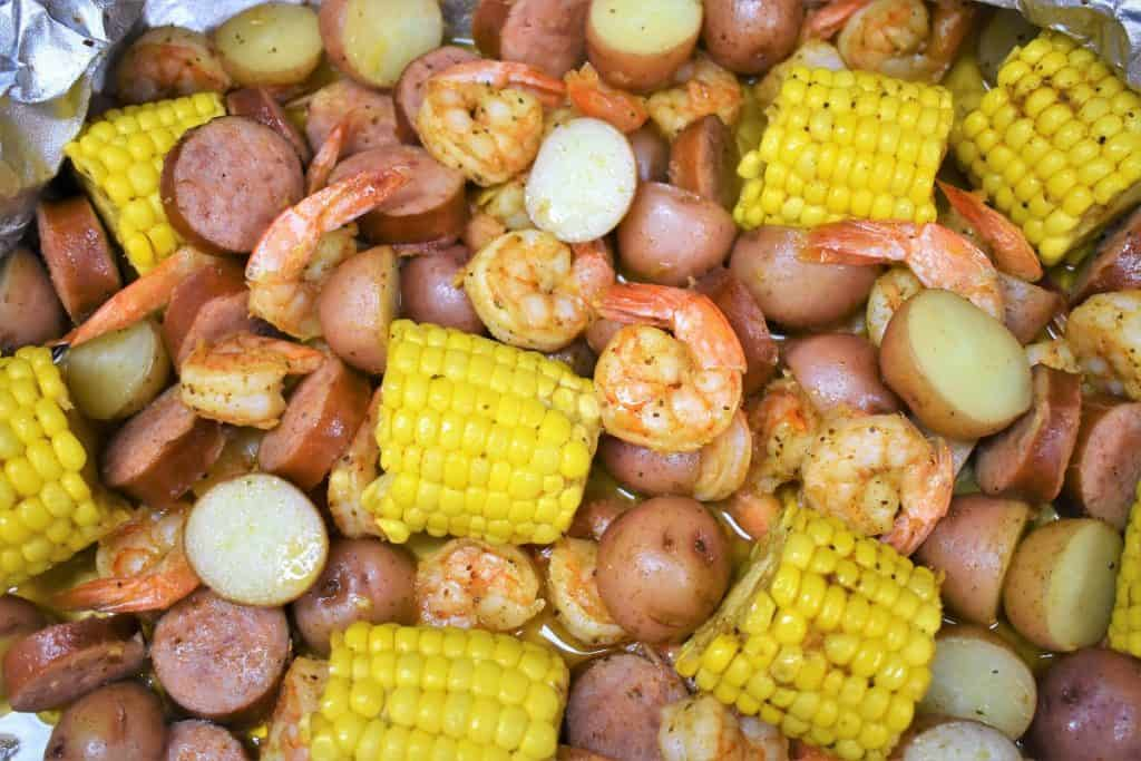 A close up of sausage, shrimp, corn and potatoes in an open aluminum foil pack.