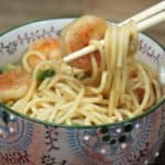 Shrimp Lo Mein noodles topped with shrimp served in a pretty bowl with chopsticks lifting the noodles and a shrimp
