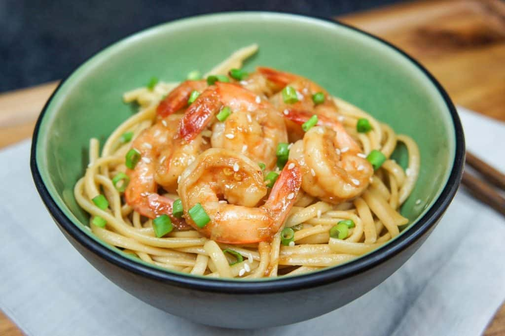 The sesame noodles topped with shrimp served in a green bowl on a beige linen on a wood table.