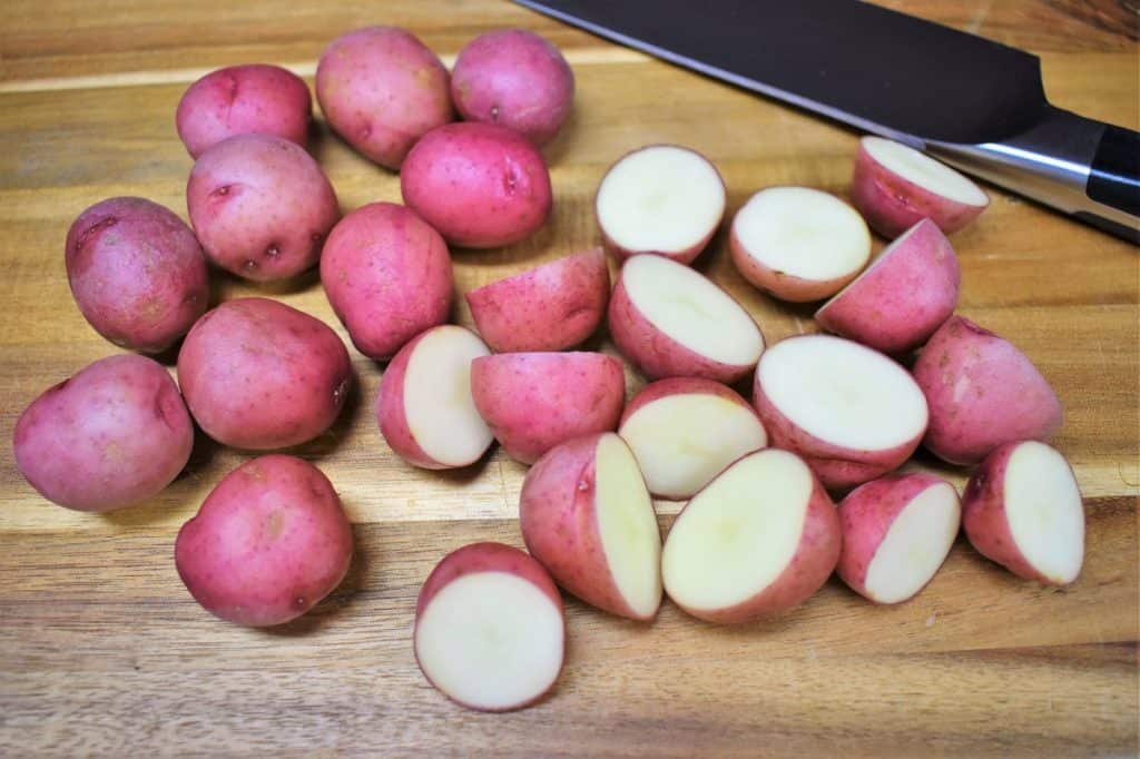 Small red potatoes, cut in half and displayed on a wood cutting board.