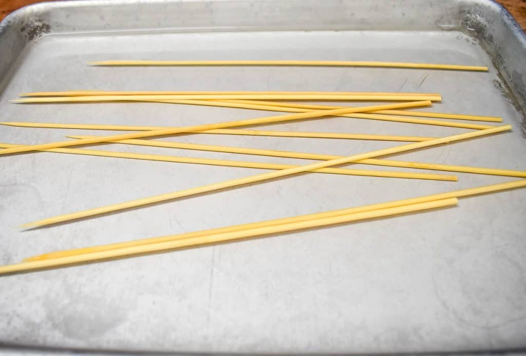 Several bamboo skewers covered with water in a metal sheet pan.