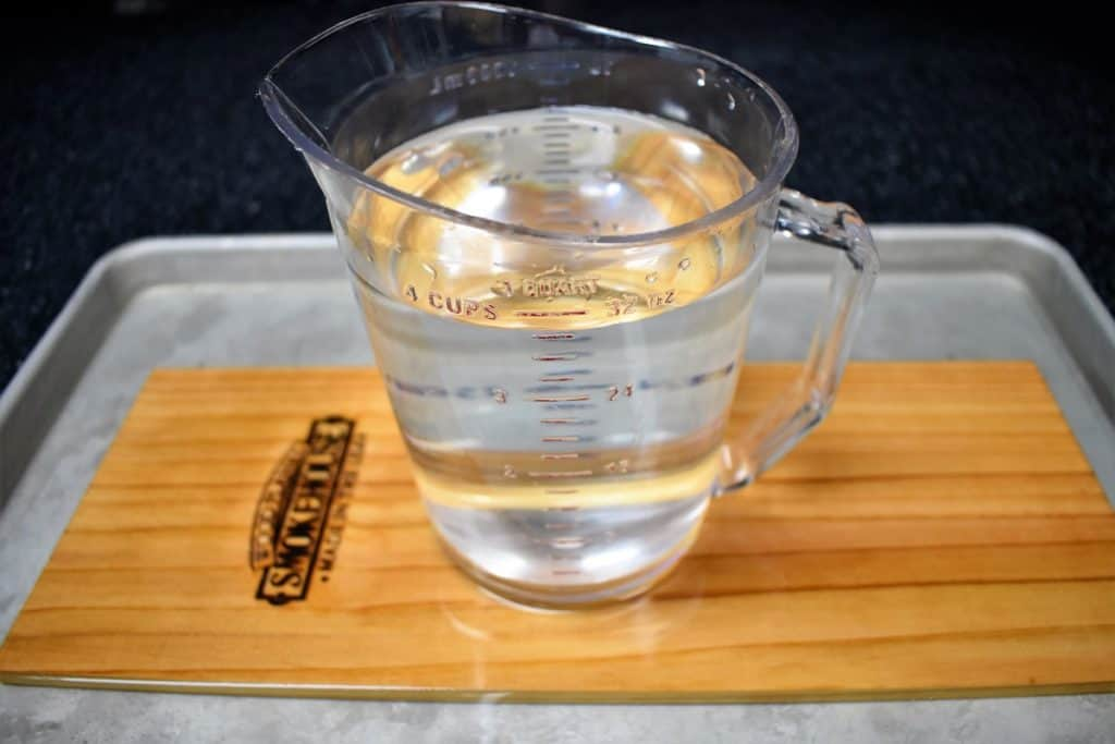 A cedar plank covered with water with a large measuring cup on top to weigh it down.