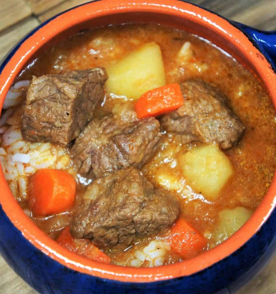 Beef soup with carrots, potatoes and white rice served in a blue crock.