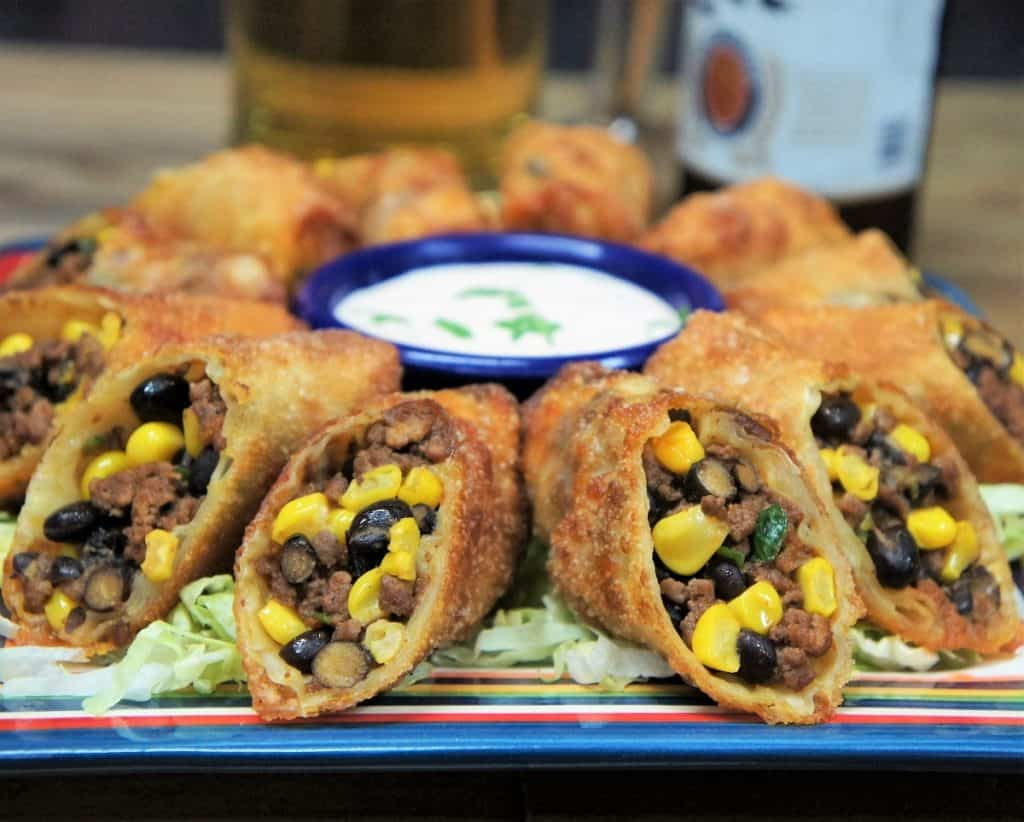 Southwestern egg rolls cut in half and arranged on a plate with a sour cream dipping sauce in the center.