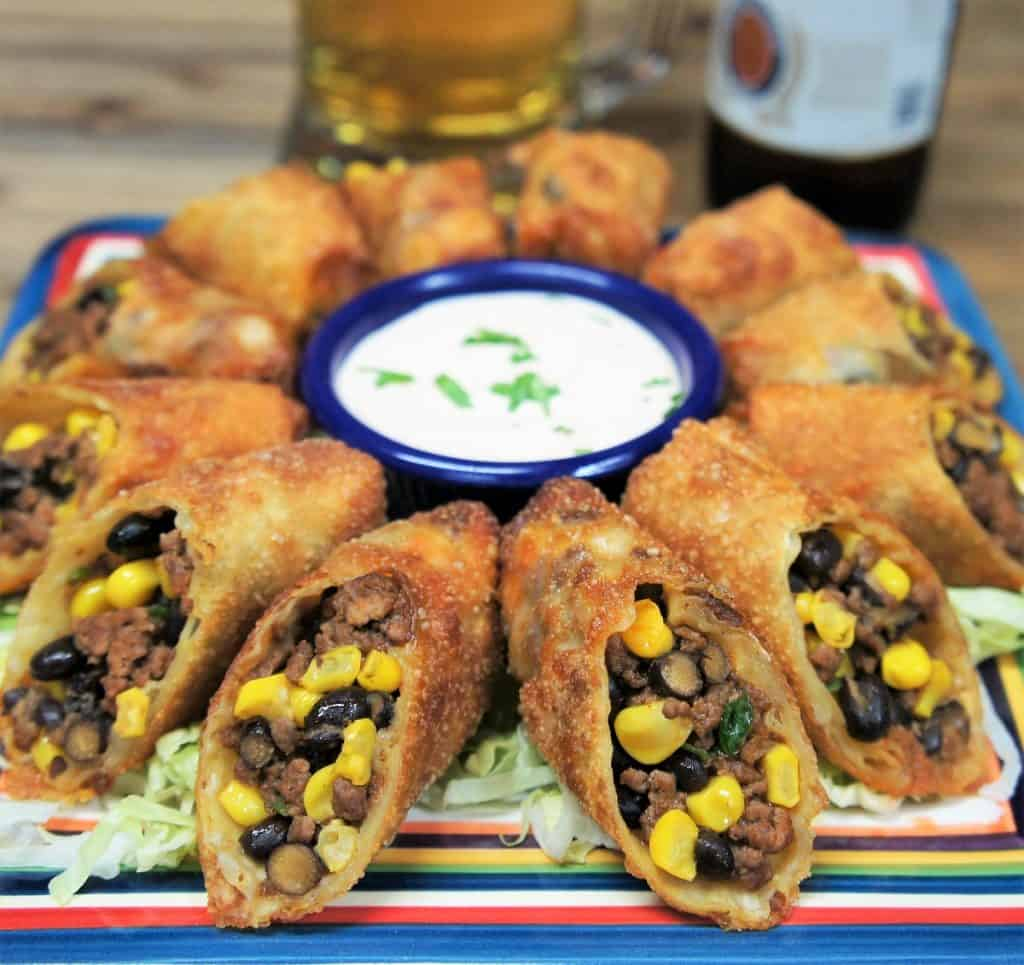 Southwestern egg rolls, cut in half and arranged on a platter with sour cream for dipping.