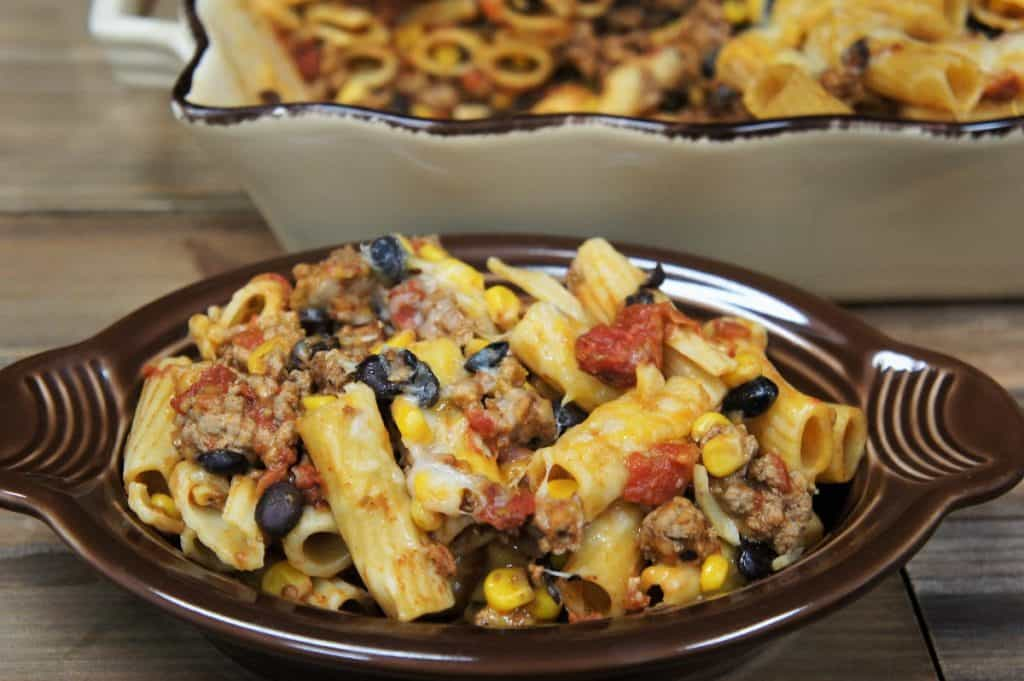 Southwestern Pasta in a brown bowl topped with melted cheese, black beans and corn