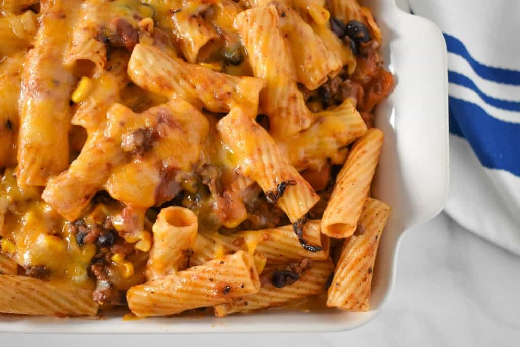 An image of the baked southwestern pasta in a white casserole dish with a blue and white kitchen towel.