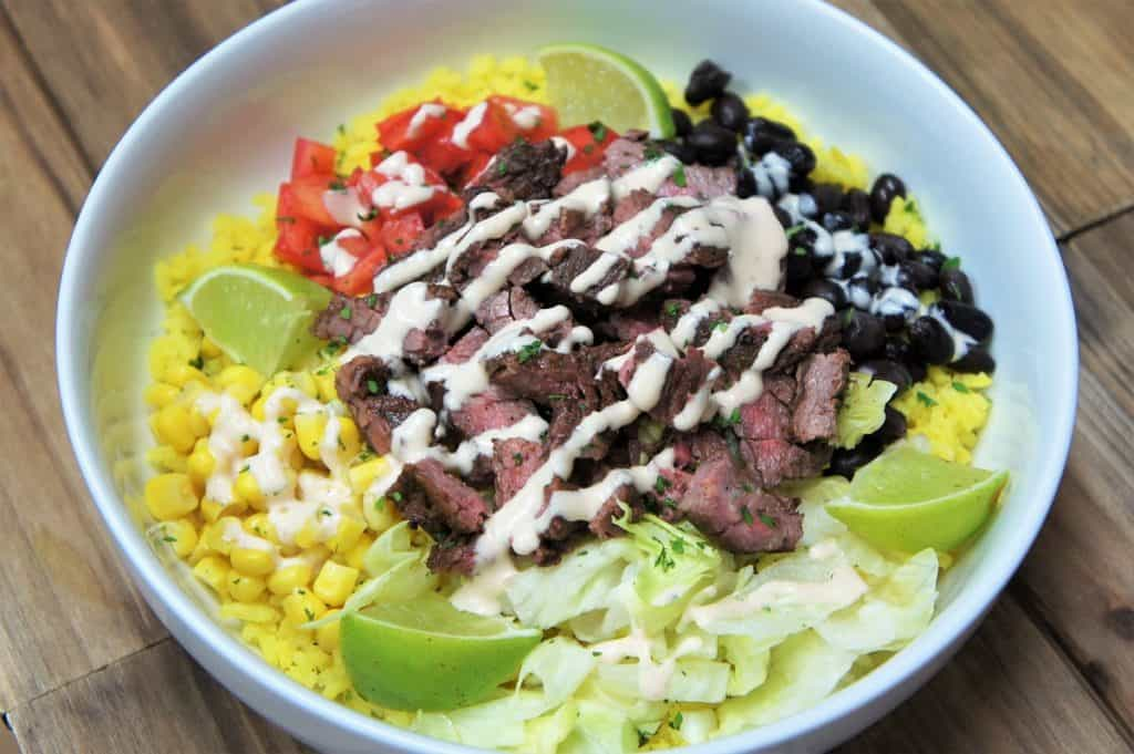 Southwestern Steak Bowl, sliced steak served on yellow rice, with black beans, corn, diced tomatoes, shredded lettuce and lime wedges all arranged on a white plate