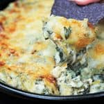 Spinach and artichoke dip served in a black skillet with some being scooped by a blue tortilla chip.