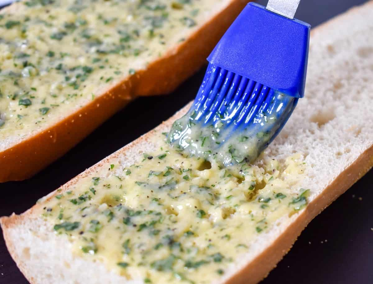 A blue pastry brush applying garlic butter to a loaf of bread that is sliced in half.