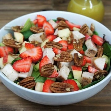Spring Chicken Salad, a white large bowl with with lettuce topped with chopped chicken, sliced strawberries, diced red apples and pecans, with a bottle of dressing in the background
