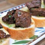 Cubes of sirloin steak on small toast rounds arranged on a colorful platter.