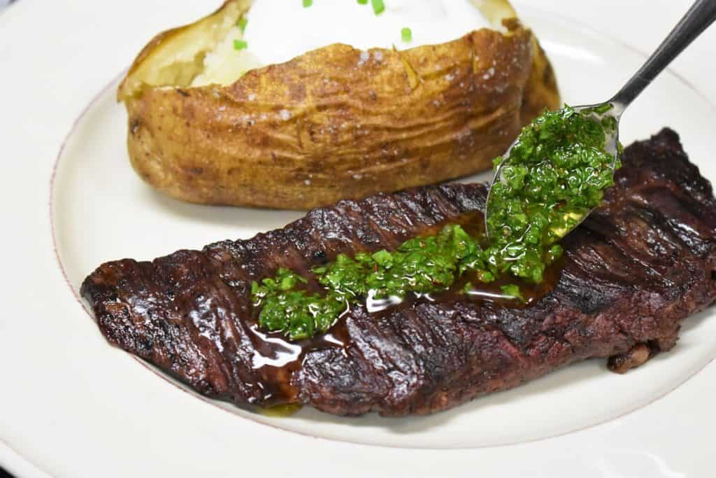 A steak with chimichurri sauce on top with a baked potato in the background