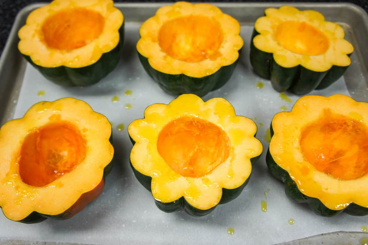 Six squash halves drizzled with olive oil arranged on a large baking sheet lined with parchment paper.