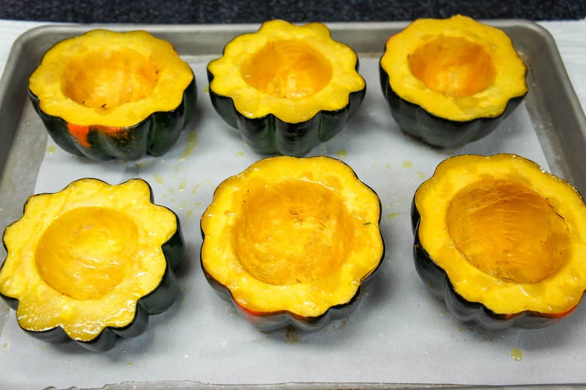 Six squash halves after baking arranged on a large baking sheet lined with parchment paper.