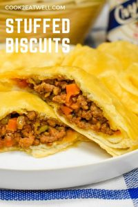 A baked biscuit stuffed with ground beef, cut in half and served on a white plate with potato chips.
