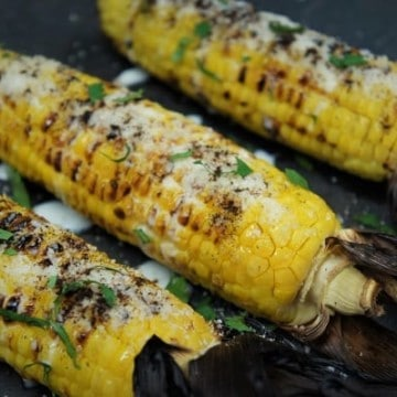 Grilled Corn served on slate board and topped with parmesan cheese, crema and chopped cilantro