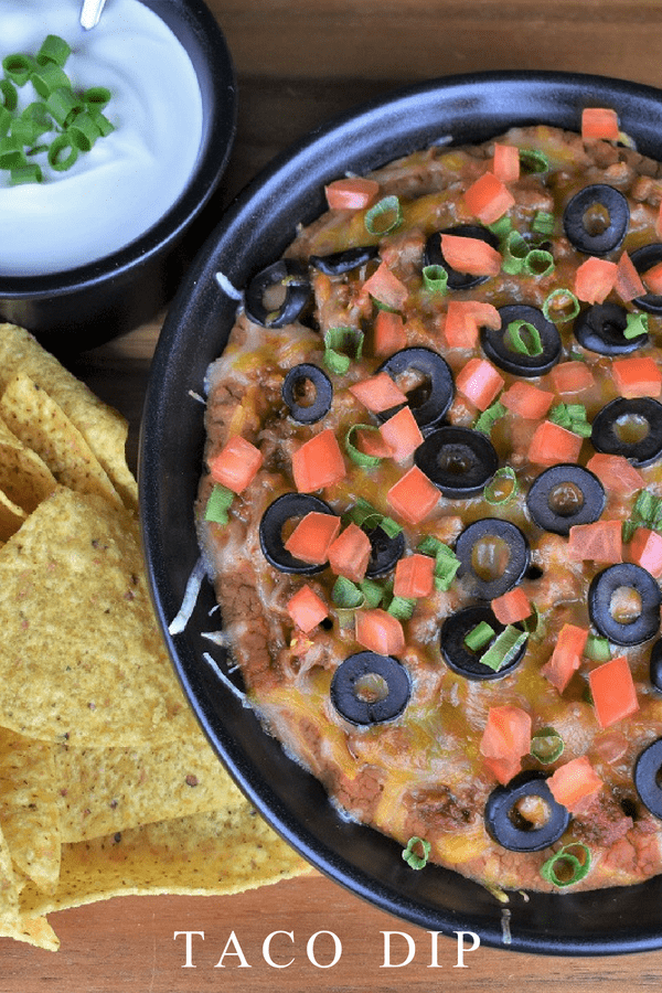 This taco dip is a great alternative for taco night. It also makes a delicious appetizer for your next game-day spread. This dip is quick and easy. It's made with lean ground turkey instead of beef, but don't worry, the flavor is all there. The taco meat is generously layered with refried beans, cheese, black olives, green onions and tomatoes, making it hearty and delicious. #tacodip #tacos #gamedayappetizers #taconight #groundturkey #appetizers #partyfood #easyappetizers