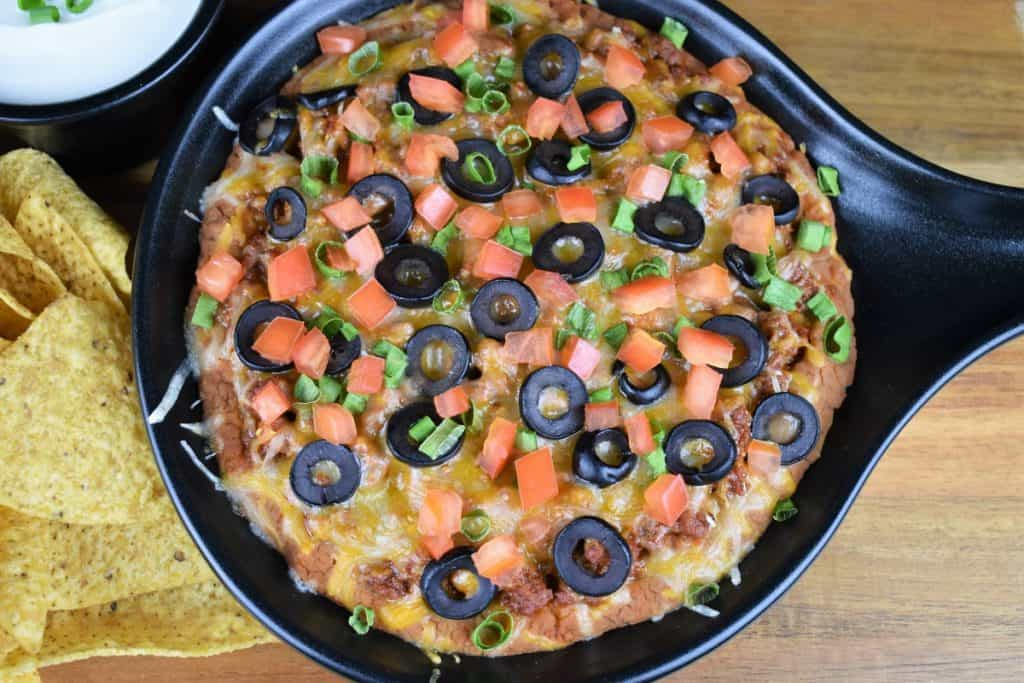 Taco Dip, refried beans and seasoned ground turkey topped with melted cheese, diced tomatoes, black olives and green onions served in a black bowl with corn tortilla chips and sour cream on the side.