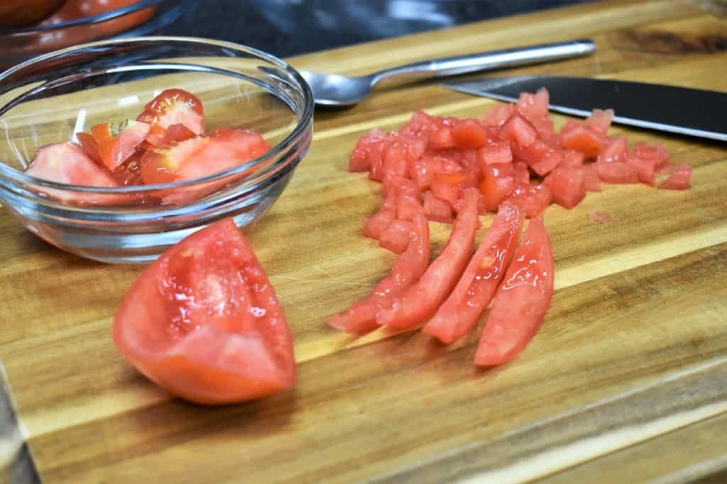 A tomato on a wood cutting board that has been seeded, cut into strips and diced.