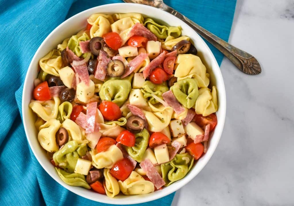 The tortellini pasta salad served in a large white bowl, displayed on a white table with an aqua colored linen underneath and a serving spoon in the background.