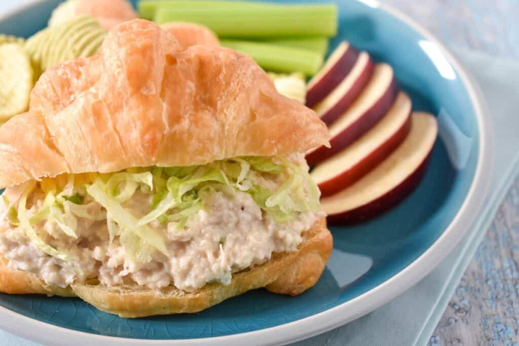 Tuna salad topped with shredded lettuce on a croissant with sliced apples and celery sticks on the side. The sandwich is served on a blue plate.