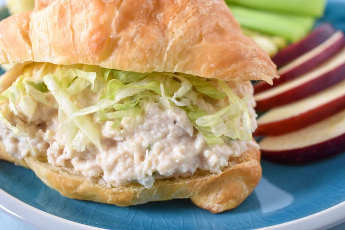 A close up image of the tuna salad served on a croissant topped with shredded lettuce with sliced apples and celery sticks on the side.