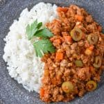 The picadillo served with white rice on the side on a gray plate and garnished with parsley leaves.