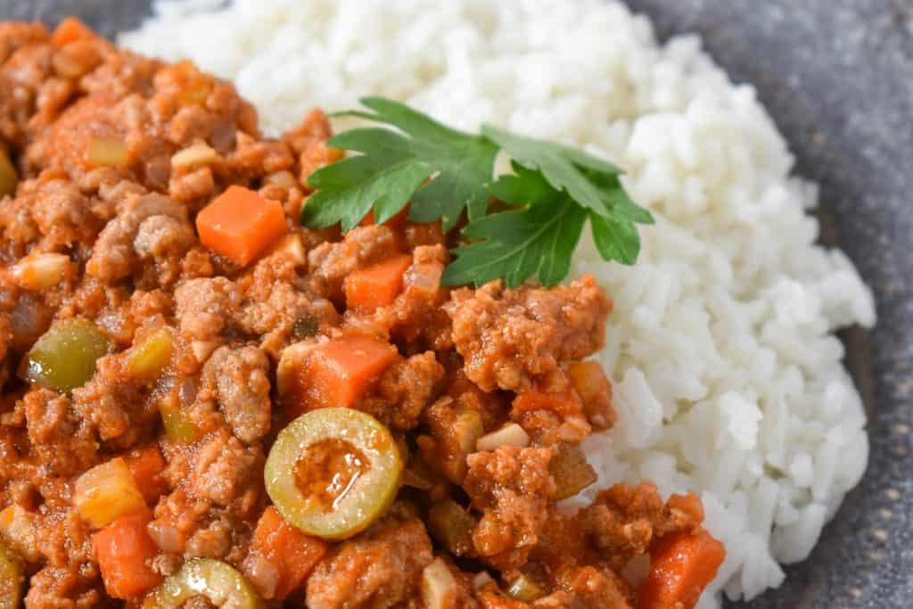 A close up image of the picadillo, served with white rice and garnished with parsley.