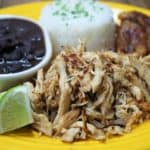 Vaca frita de pollo shredded crispy chicken with mojo marinade served on a yellow plate with white rice, black beans and fried sweet plantains on the side