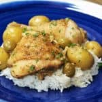 White chicken fricassee, stewed chicken with whole baby potatoes, green olives on a bed of white rice, served on a blue plate