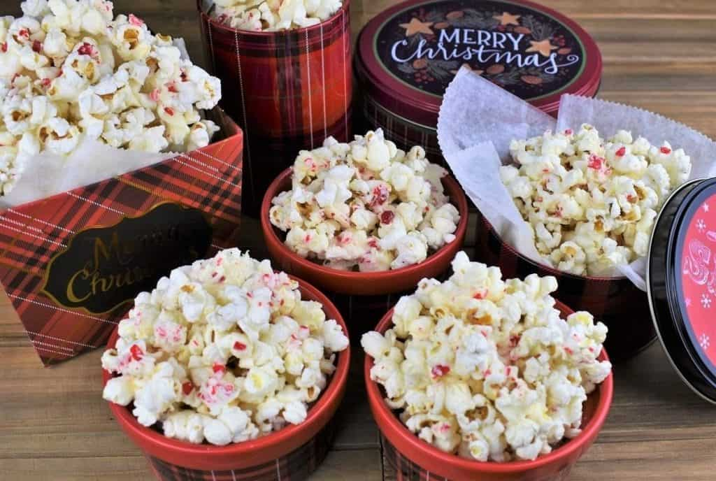 White Chocolate Peppermint Popcorn served in Christmas themed tins and bowls