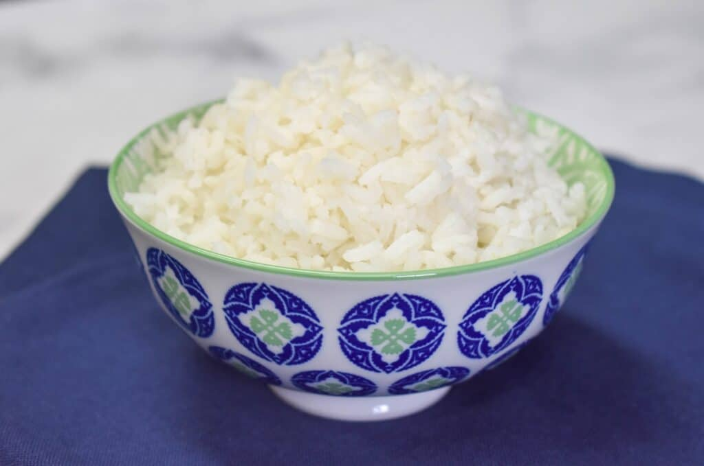 White rice mounded in a small, decorative blue and white bowl, displayed on a blue linen.
