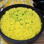 Yellow rice served in a large black serving bowl.