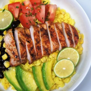 Yellow Rice + Grilled Pork Loin Bowl, a bed of yellow rice topped with grilled, seasoned pork loin, corn, black beans, sliced avocados and diced tomatoes, garnished with sliced limes
