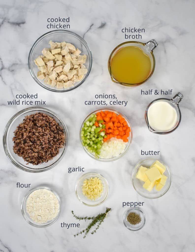 The ingredients for the chicken and wild rice soup prepped and arranged in glass bowls on a white table. Each ingredient is labeled with small letters.