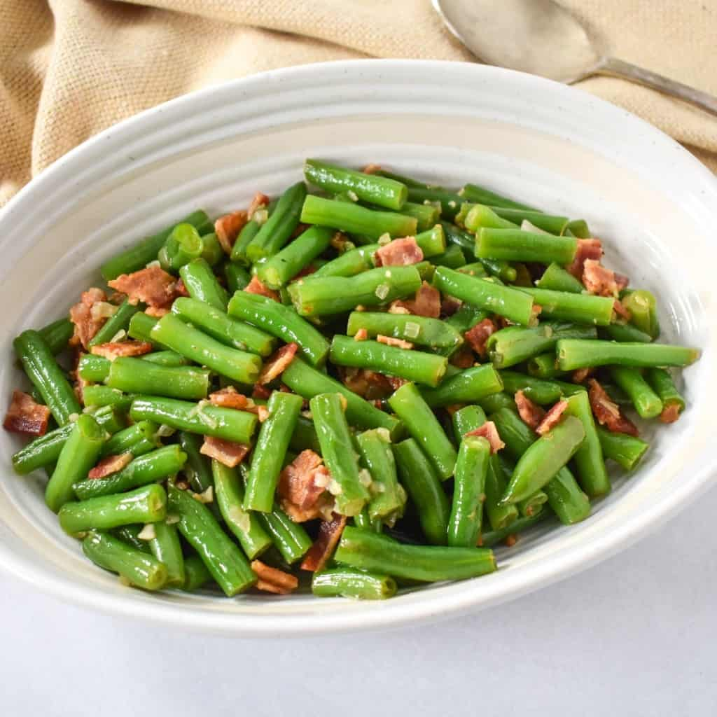 An image of the green beans with bacon served in an oval white bowl with a beige linen and a serving spoon to the right.