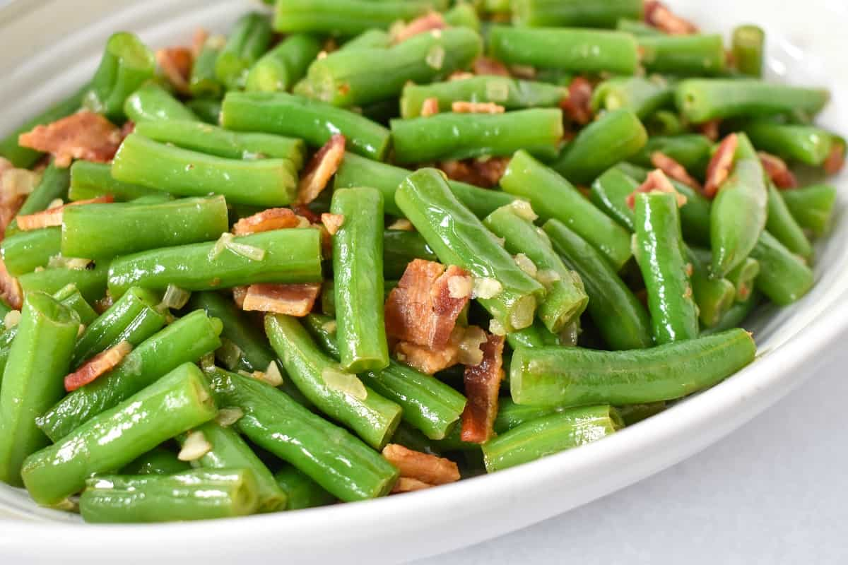 A close up of the bacon green beans served in a white bowl.