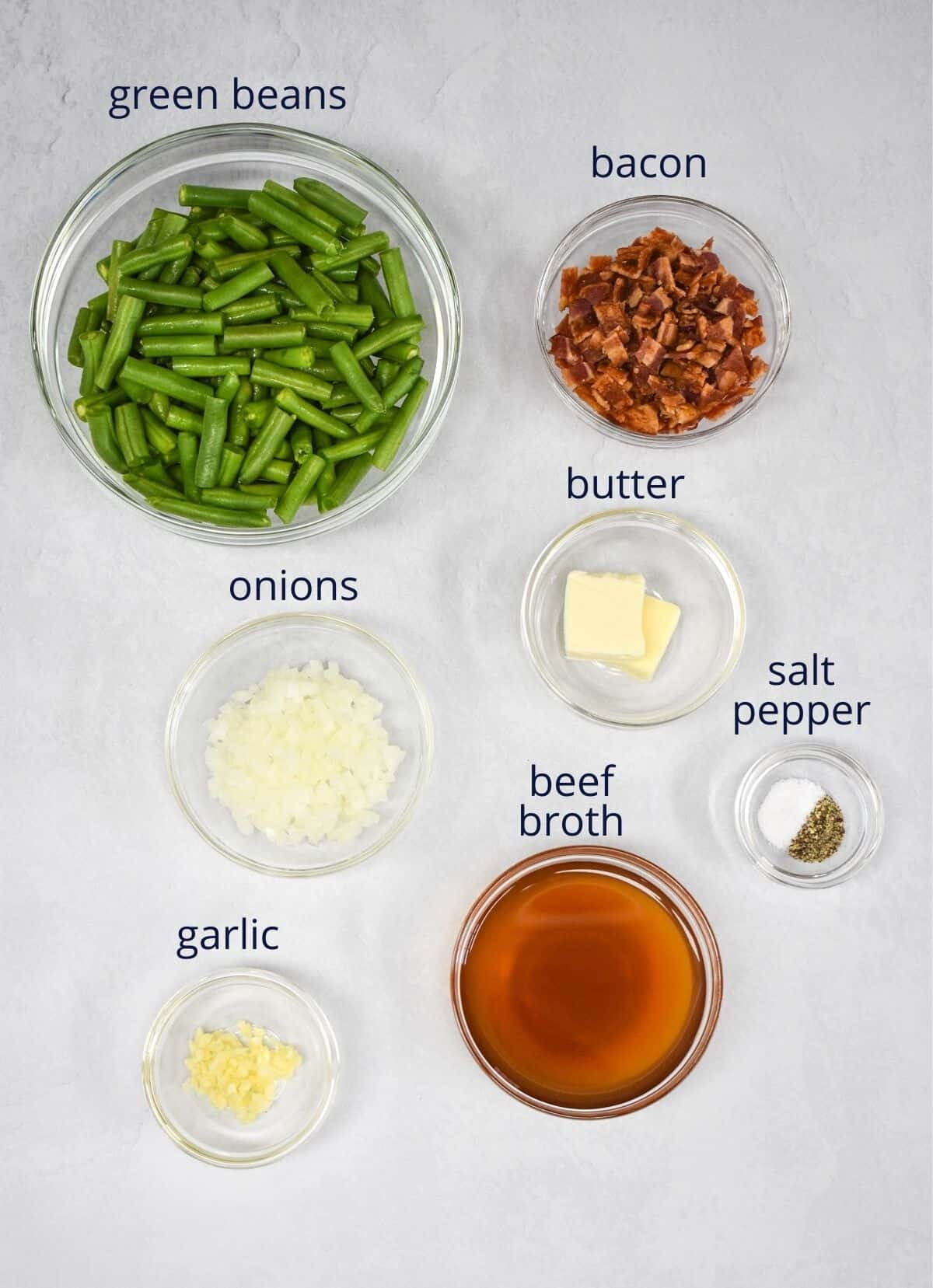 The ingredients for the side dish arranged in glass bowls on a white table. Each ingredient has a small label with the name on top.