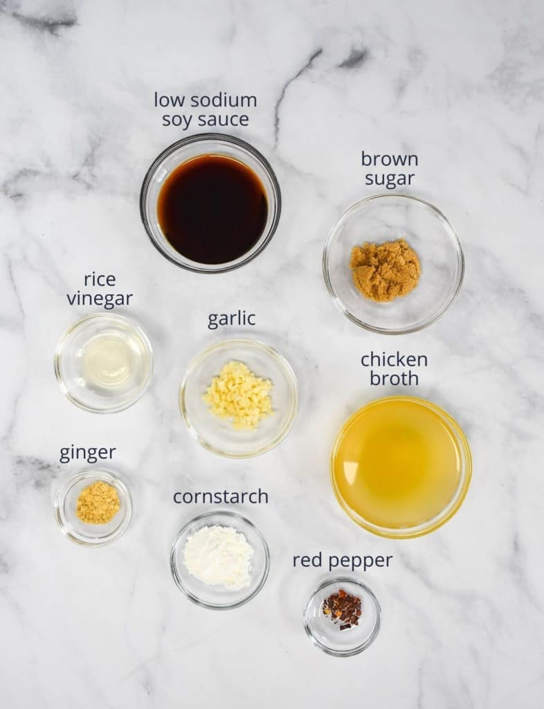 The ingredients for the sauce arranged in small glass bowls and arranged on a white table.