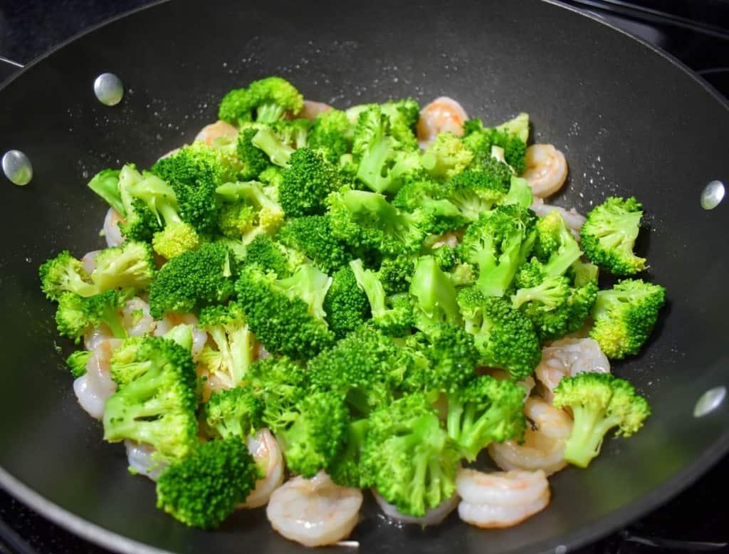 An image of broccoli florets added to shrimp in a large, black skillet.