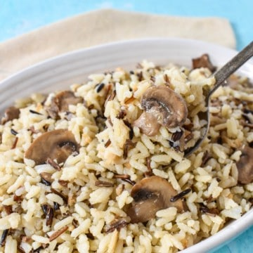 An image of the mushroom rice pilaf served in a white bowl with a beige linen and set on a light blue table.