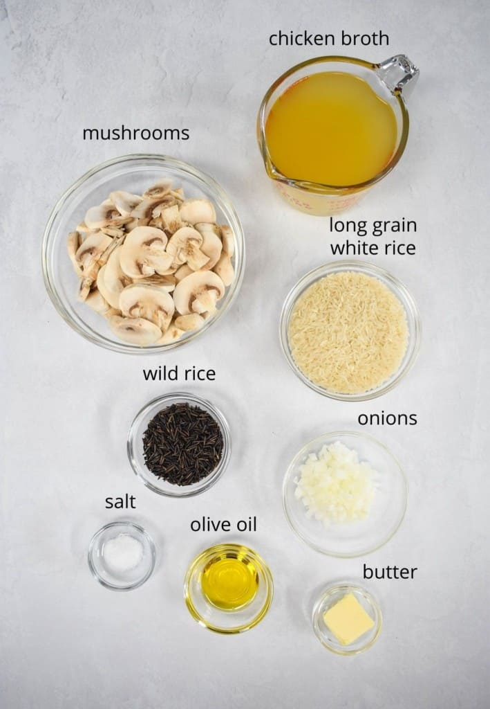 The ingredients for the rice dish, prepped and separated in glass bowls, displayed on a white table. Each ingredient is labeled in small black letters.