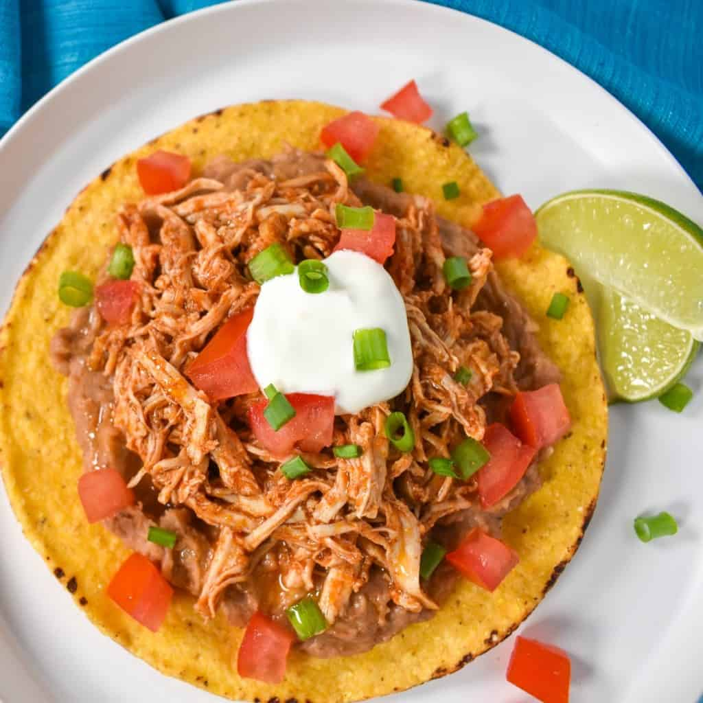 An image of the shredded chicken tostada on a white plate and garnished with diced tomatoes, sour cream and sliced green onions with two lime wedges on the side.