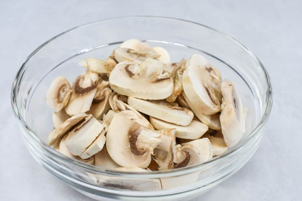 An image of sliced mushrooms in a glass bowl, set on a white table.