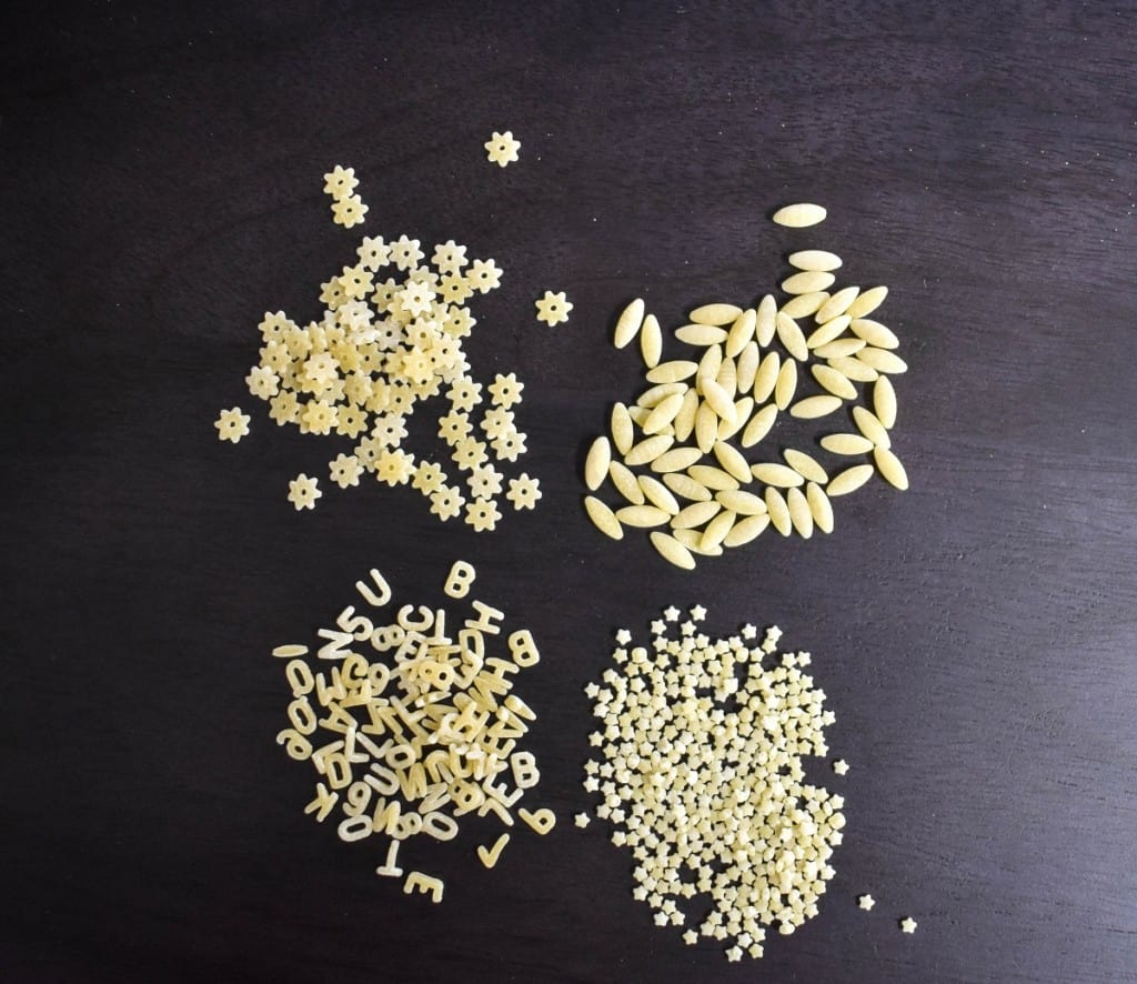 An image of four types of pastina displayed on a dark brown board.