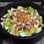 Asian Chopped Salad, topped with crunchy rice noodles, sliced almonds, and chopped grilled chicken served in a black bowl.