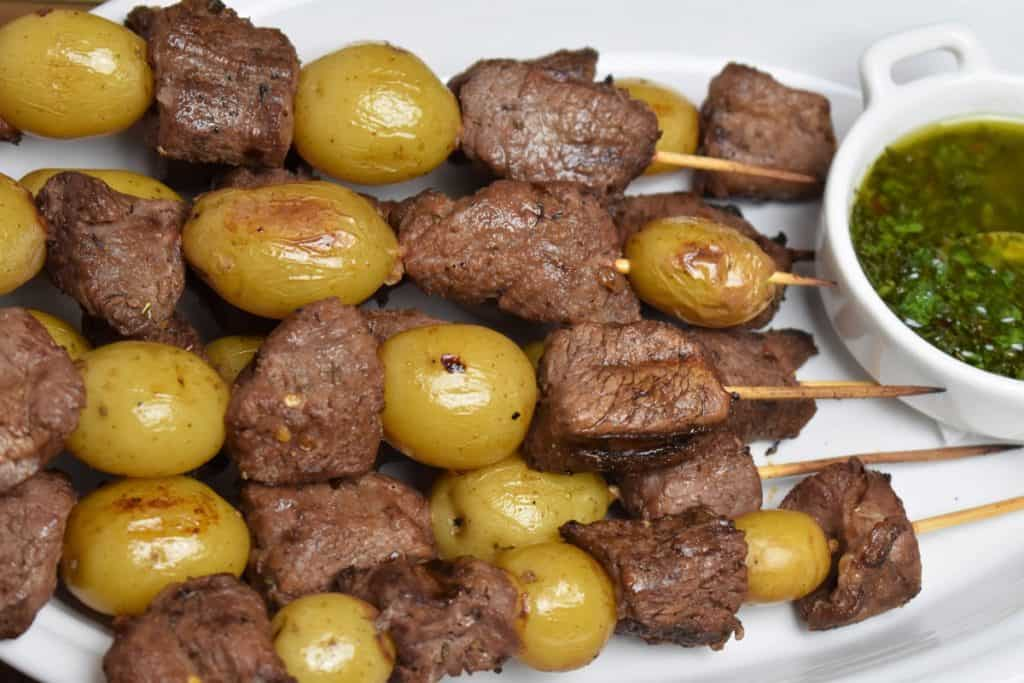 Beef & Potato Skewers served on a white platter with chimichurri sauce on the side
